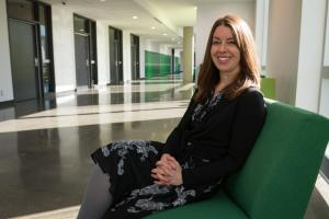 Smiling woman faces the camera, seated upon a green chair in a long corridor at an academic institution. She is dressed in a black blazer and patterned dress.