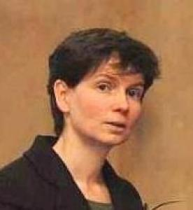 A woman faces the camera, her body tilted slightly away. She is wearing a brown top and is against a light brown background. She has short brown hair.