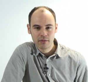 Man stares at the camera, against a light blue backdrop. He is wearing a grey shirt.