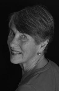 a woman looks back over her shoulder to the viewer and is smiling. The image is in black and white.